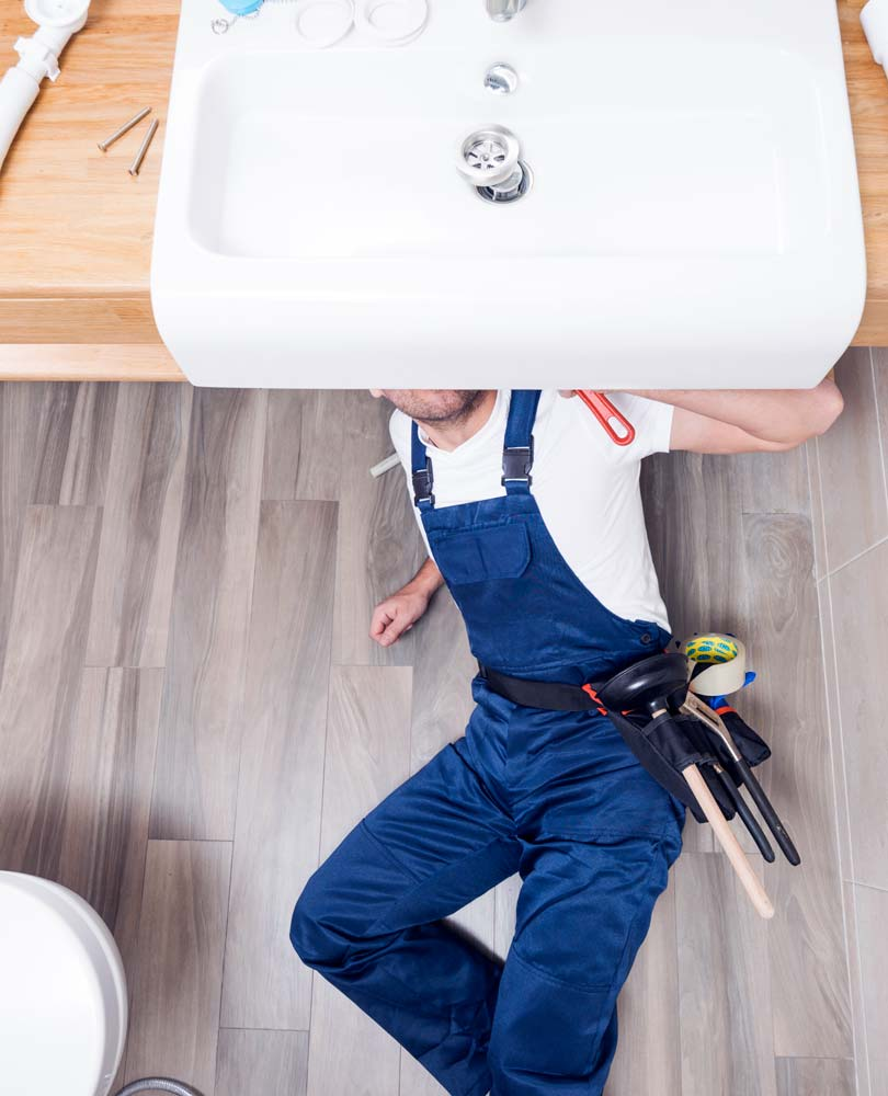 Plumber under sink making repairs